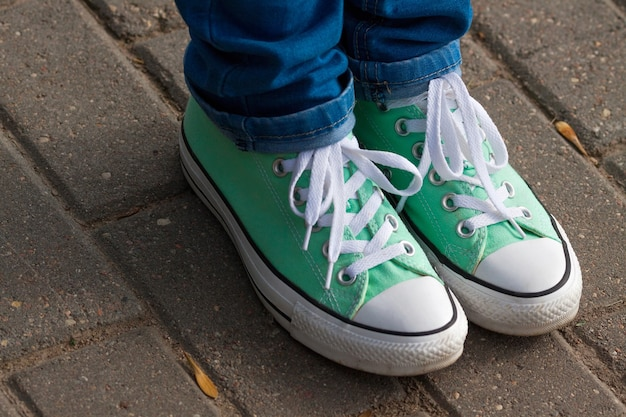 Mint youth sneakers, shod on feet in blue jeans, on paving city tiles, diagonal arrangement of sneakers