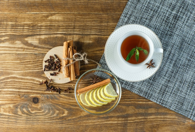 Minty tea with biscuits, cloves, lemon slices, cinnamon sticks in a cup on wooden surface