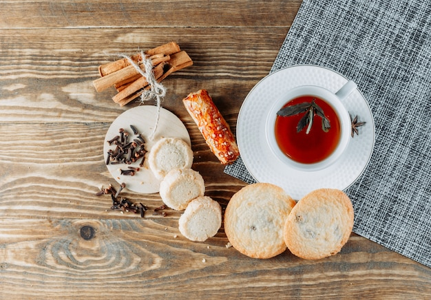 Minty tea with cinnamon sticks, biscuits, cloves in a cup on wooden surface