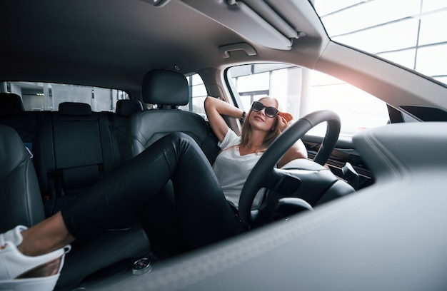 Minute of relaxation. girl in modern car in the salon. at daytime indoors. buying new vehicle.