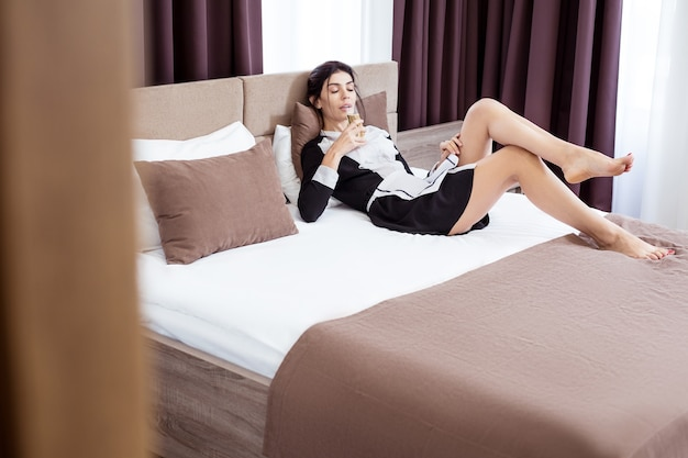 リラックスする分。ベッドに横たわっている間シャンパンを飲む素敵な若いホテルのメイド