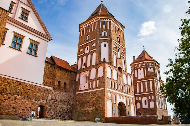Mir, belarus. view of a medieval castle on a background of blue sky. summer panoramic landscape