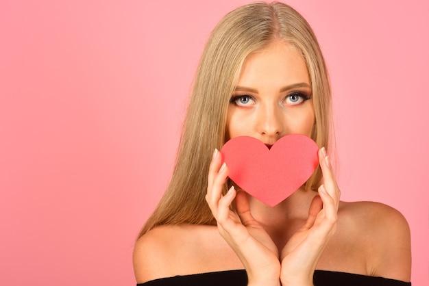 奇跡、愛の魔法。手にバレンタインの心を持つファッションモデルの女の子。メイク、バレンタインデー、愛とファッションのコンセプト-シンボルバレンタイン赤いハートを保持している完璧なメイクで魅力的な女性。