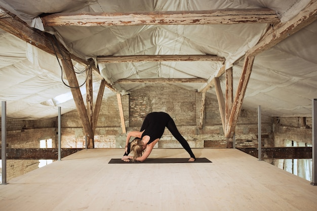 거울. 젊은 체육 여자 버려진 된 건설 건물에 요가 연습. 정신적 및 신체적 건강 균형. 건강한 라이프 스타일, 스포츠, 활동, 체중 감소, 집중력의 개념.