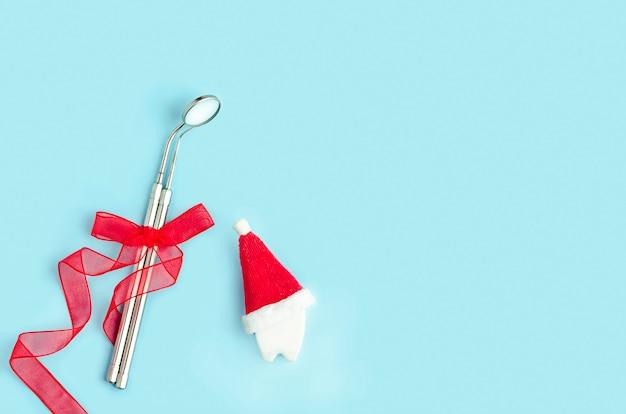 鏡とプローブ、新年の赤いリボン付きの歯科用ツール、青い背景のサンタ帽子の歯。クリエイティブメディカルクリスマスストマトロジー冬