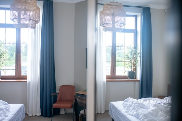 Зеркало, спальня. неубранная кровать с белым одеялом, окном и кожаным креслом, отражающимся в зеркале при дневном свете