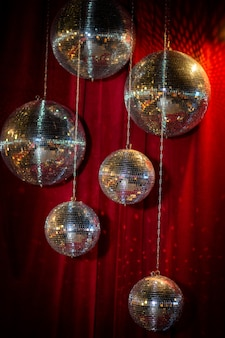 Mirror disco balls against the background of a red velvet curtain