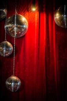 Зеркальные диско-шары на фоне красной бархатной занавески