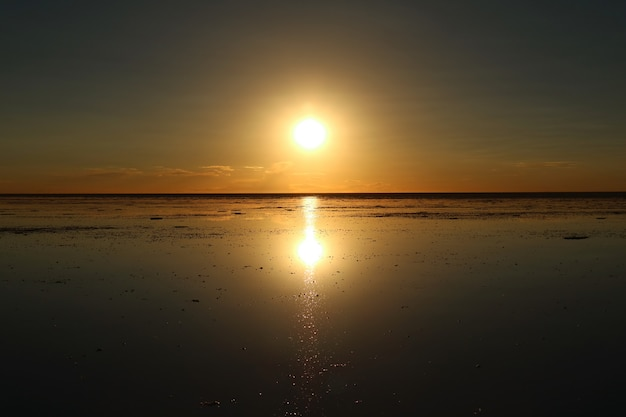 Mirror effect of the setting sun at uyuni salt flats or salar de uyuni in bolivia, south america