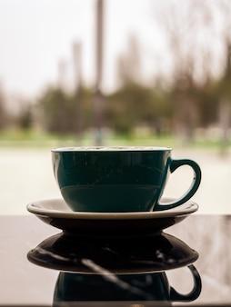 テーブルの暗い表面にある美しいスタイリッシュなマグカップの鏡像