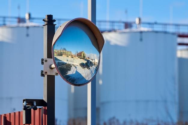Зеркало сферического типа на телеграфном столбе, отражающее дорогу. большое выпуклое зеркало на дороге для улучшения обзора. выпуклое зеркало для безопасности на дороге. стекло дорожное изогнутое.