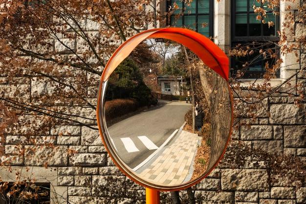 Зеркало на дороге для наглядности. в отражении девушка в осеннем парке. крупный план. сеул, южная корея, 01.04.2018.