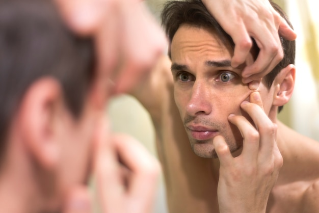 Mirror portrait of man popping a pimple