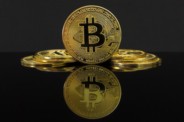 A mirror reflection of a big golden btc coin. the coin of bitcoin is on a black table and black. golden bitcoin isolated on black.