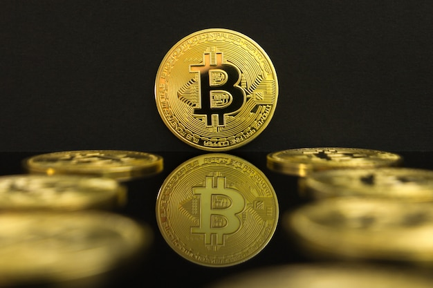 A mirror reflection of a golden btc coins. the coin of bitcoin is on a black table and black background.