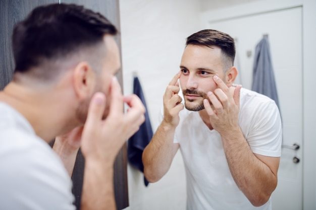 Mirror reflection of good looking caucasian man checking his wrinkles under eyes. male cosmetics concept.