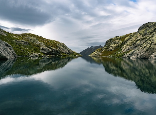 山の背景に穏やかな湖の水と空の鏡の反射