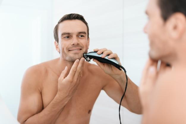 男の鏡の反射バスルームで歯を磨く