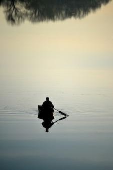 川の鏡面、ボートに座って朝釣りに行く漁師