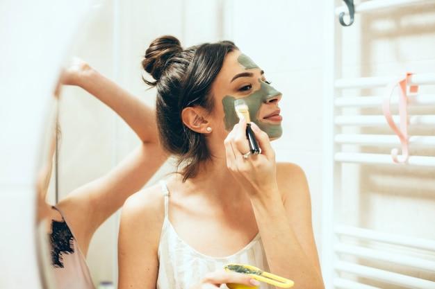 彼女の友人の近くに立っている彼女の顔に特別なマスクを適用するブルネットの女性のミラービュー
