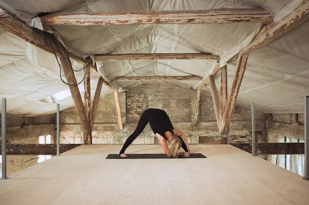 Specchio. una giovane donna atletica esercita lo yoga su un edificio abbandonato. equilibrio della salute mentale e fisica. concetto di stile di vita sano, sport, attività, perdita di peso, concentrazione.