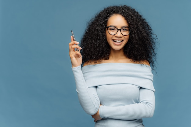 Mirthful afro american woman holds smart phone, waits for call