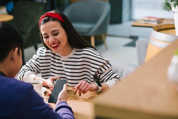 彼女と一緒にカフェのテーブルに座っている男の手でスマートフォンを笑って見ている陽気な美しい女性