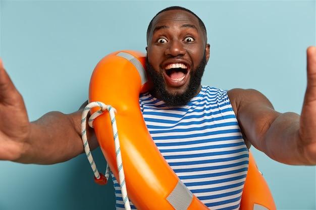 Il ragazzo afroamericano felice e allegro fissa con felicità la telecamera, fa selfie, posa con lifering