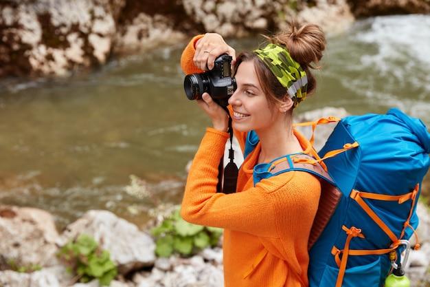 Gioiosa viaggiatrice scatta foto sulla fotocamera, si concentra sulla distanza, indossa la fascia, un maglione arancione, ammira la vista panoramica della natura