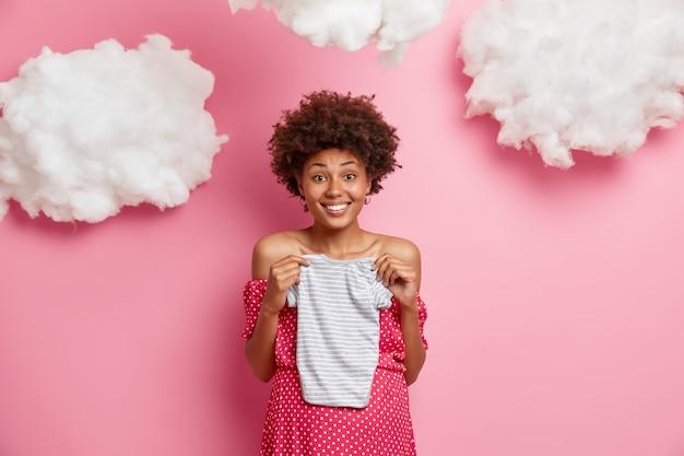 妊娠中の女性は赤ちゃんを期待し、おなかの上にボディースーツを持って、男の子が欲しい、嬉しそうに笑う、妊娠中の気分が良い、白い雲とピンクの壁に隔離