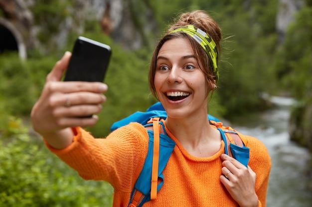 Веселая туристка с широкой улыбкой держит сотовый телефон перед собой, делает селфи-портрет