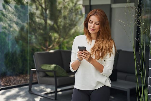 쾌활한 여성은 집에서 시간을 보내고 전화를 보고 누군가에게 메시지를 쓰는 동안 웃고 있습니다. 사람과 기술 개념