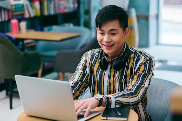 Веселый молодой человек сидит за библиотечным столом и улыбается, используя современный ноутбук