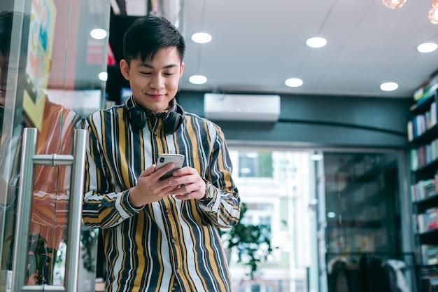 Веселый молодой человек улыбается, находясь в офисе и глядя на экран смартфона. шаблон баннера