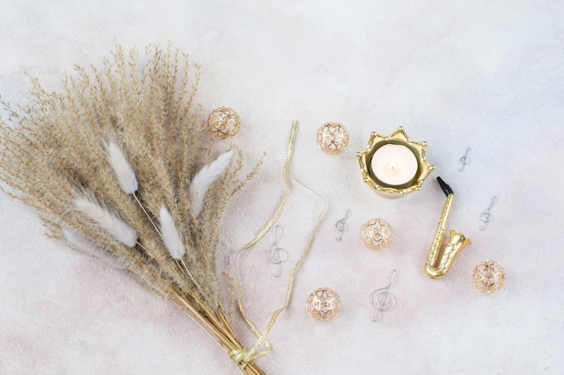 Miscanthus bouquet, saxophone, treble clefs, candle and gold decor