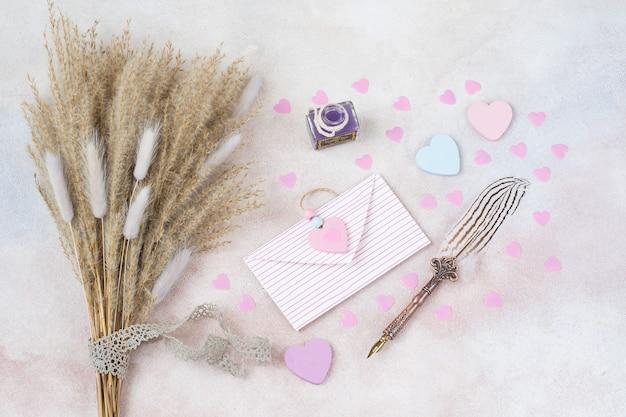 Мискантус, перевязанный кружевной лентой, сердечками, перьевой ручкой, тушью и конвертом