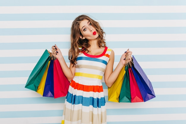 Mischievous, cheerful girl makes cute and funny face, posing with colorful paper packages. close portrait of brown-haired woman with red lipstick, happy after successful shopping