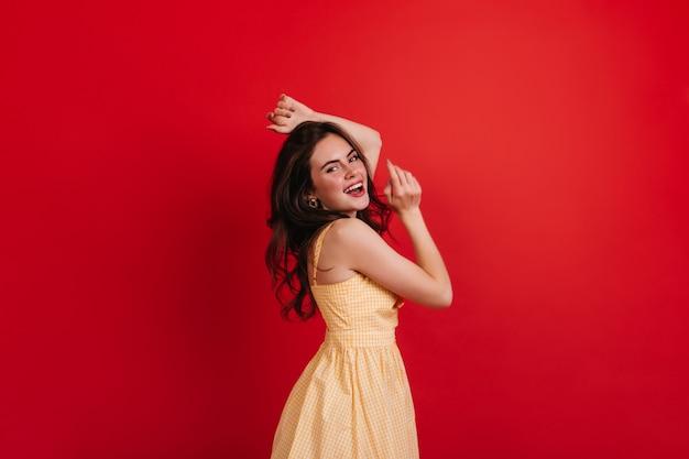 장난 꾸러기 곱슬 아가씨는 붉은 벽에 춤을 추고 있습니다. 노란색 드레스를 입은 갈색 머리가 진심으로 웃고 사진 촬영을 즐깁니다.