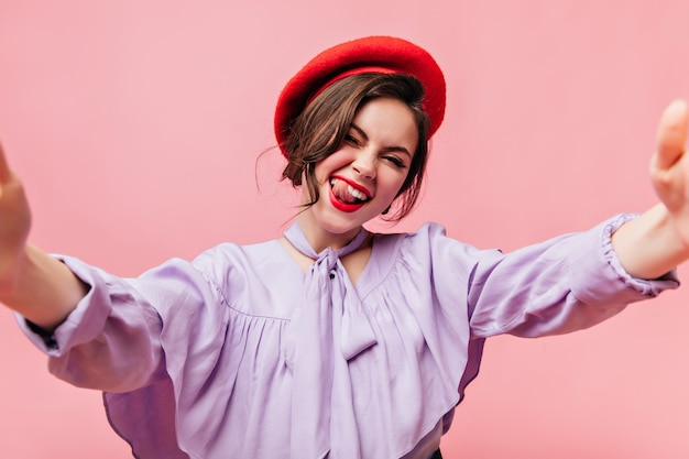 Ragazza maliziosa in berretto mostra la sua lingua. signora in camicetta viola fa selfie su sfondo rosa.