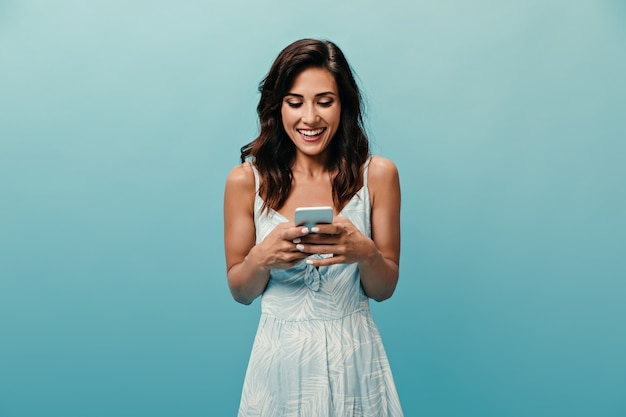 Озорная девушка в белом платье с улыбкой болтает в смартфоне на синем фоне. веселая милая женщина в хорошем настроении держит телефон.
