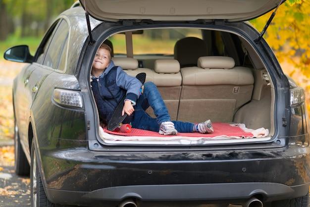 Озорной маленький мальчик со скейтбордом сидит в багажнике автомобиля и счастливо улыбается в камеру на улице на улице осенью