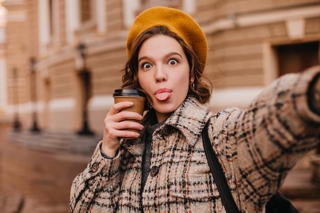 가을 옷을 입은 장난 꾸러기 여자가 도시 벽에 셀카를 만든다.