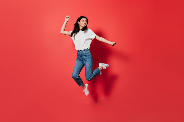 Mischievous woman in white t-shirt and jeans jumping on red wall