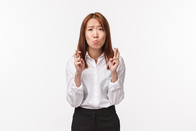 Miserable and desperate cute asian woman cross fingers good luck, nervously and impatiently  with pleading eyes, making wish, praying for dream come true