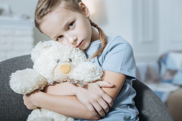 Miserable fair-haired blue-eyed little girl hugging and holding her teddy bear while sitting in the armchair