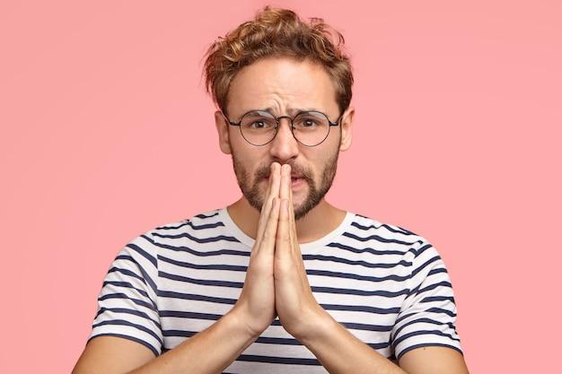 Несчастный человек с умоляющим выражением лица просит об одолжении, держит руки в молитвенном жесте