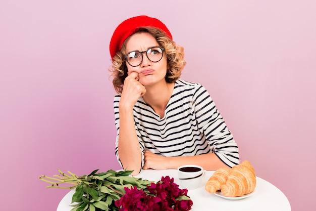 悲惨な気分を害した不満のかわいい女の子は、ピンクのコーヒーとクロワッサンでテーブルのそばに一人で座っている唇を曲げます。