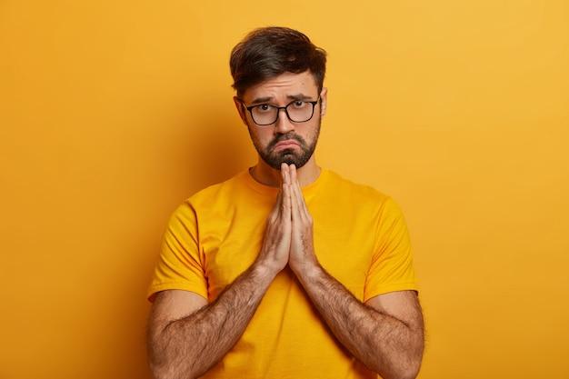 비참한 슬픈 탄원하는 남자는 진심으로 부탁하고, 사과하고, 손바닥을 함께 누르고, 화가 난 표정으로 구걸하고, 문제에 도움이 필요하고, 희망을 가지고기도하고, 노란색 티셔츠를 더 잘 입는 것에 대한 믿음이 있습니다.
