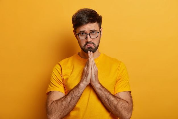 Miserable sad pleading man says sincere please, makes apology, keeps palms pressed together, begs with upset expression, needs help in trouble, prays with hope has faith in better wears yellow t shirt