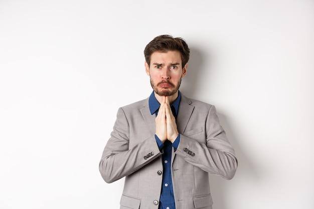 Несчастный ноющий бизнесмен, просящий ссуду, нуждается в помощи и умоляет вас, рыдая и говоря «пожалуйста» с грустным лицом, стоя на белом фоне, просите прощения.